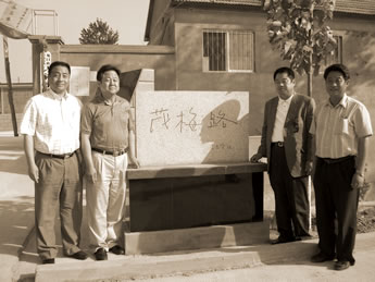 In front of the stone marker named 茂梅路after the founder's father